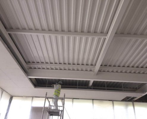 Spraying the metal ceiling of the large industrial unit in Milton Keynes